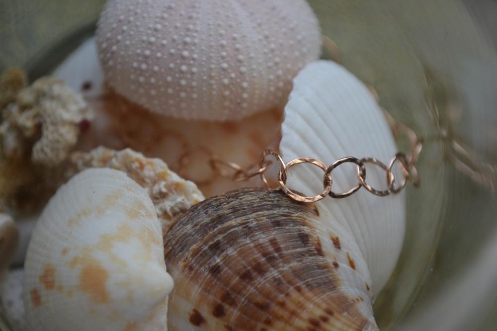 A delicate rose gold bracelet resting on seashells
