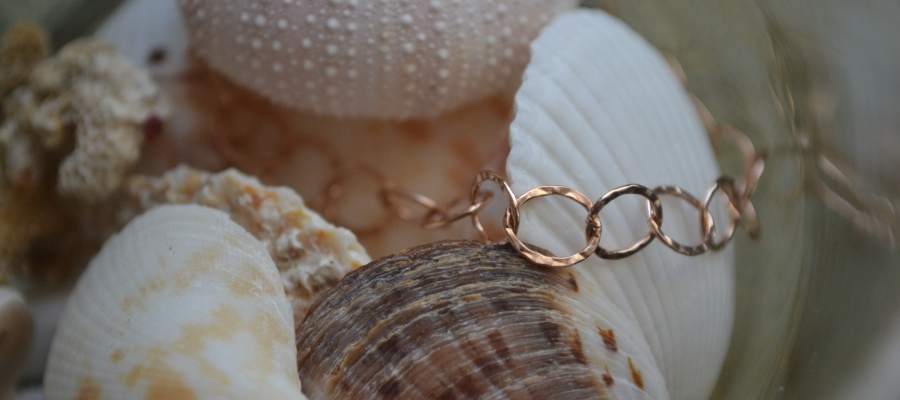 A delicate rose gold bracelet resting on seashells